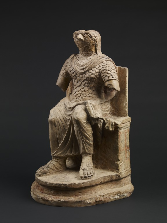 Seated figure of the ancient Egyptian god Horus, wearing Roman military costume, limestone, Egypt, 1st–2nd century AD © The Trustees of the British Museum.